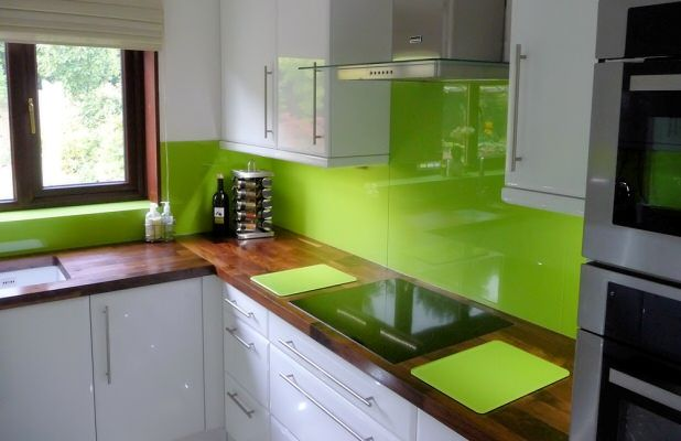 Photograph of kitchen fitted with Opticolour lime green glass splashbacks & showing matching chopping board & matching window sill