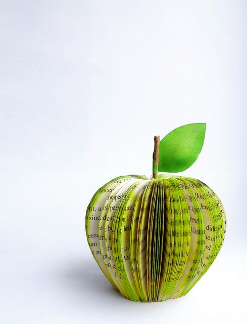 "Make a cute gift for a teacher by using a green highlighter and old book pages to create an ""apple"" for their desk"