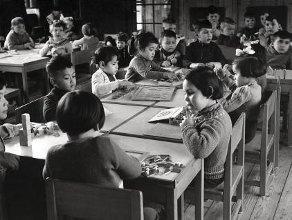 Repatrianten/spijtoptanten. Jonge evacués uit Indonesië aan een aparte tafel in een schoolklas in Amsterdam Slotermeer. De jongens en meisjes spelen o.a. met blokken en legpuzzels. Nederland, Amsterdam, 1956.
