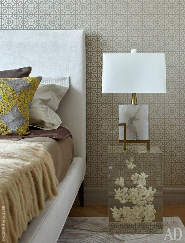 Стены спальни отделаны обоями Sussex Opal коллекции Nabucco от Designers Guild. Прикроватный столик Kisimi от Bleu Nature выполнен из плексигласа c кораллом, на кровати меховой плед фигурной вязки, Home Concept.