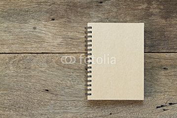 Brown notebook on wooden background.