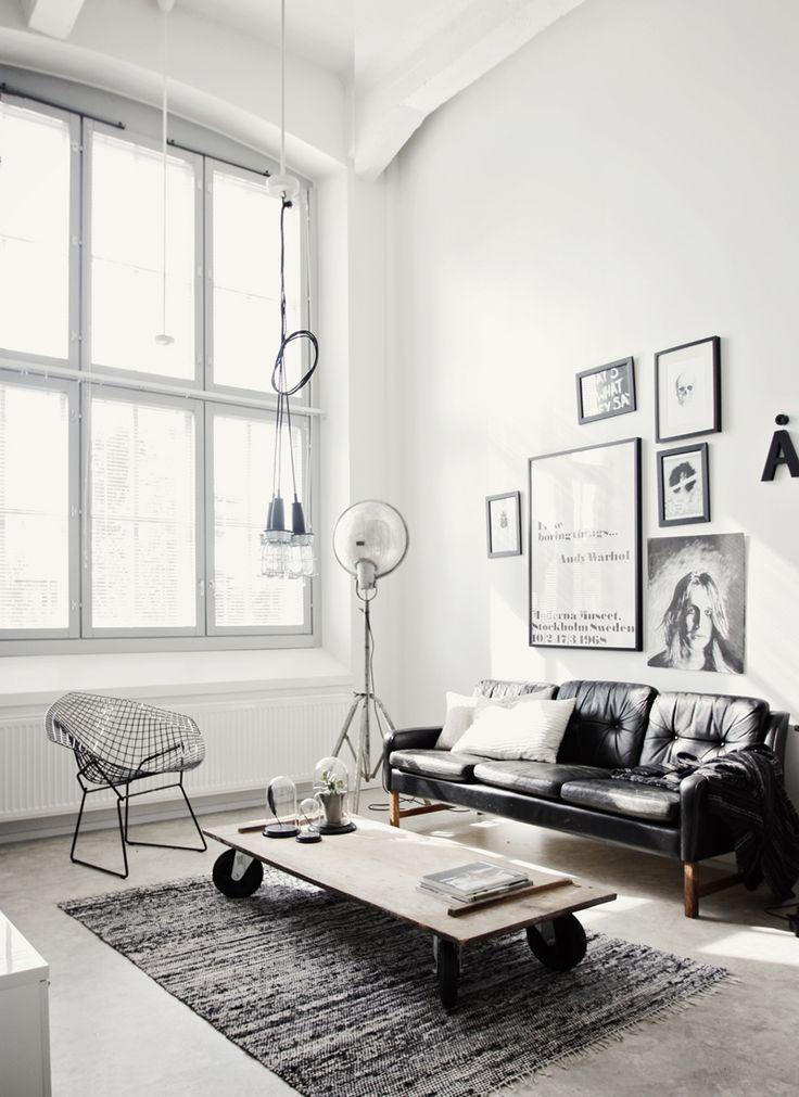 Un salon à l'esprit loft en noir et blanc, vraiment réussi. Le juste équilibre entre l'industriel (table basse sur roues, suspensions,...) et un côté plus chic (canapé en cuir noir, photos en noir et blanc aux murs), le tout baigné de lumière...