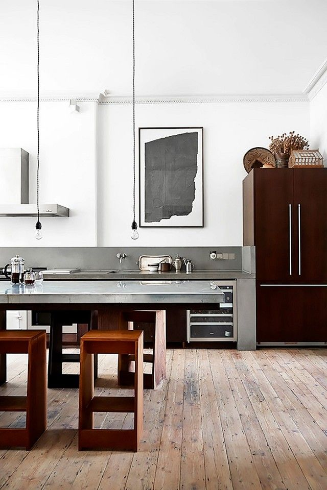 Sleek kitchen with a steel counter top and simple pendants