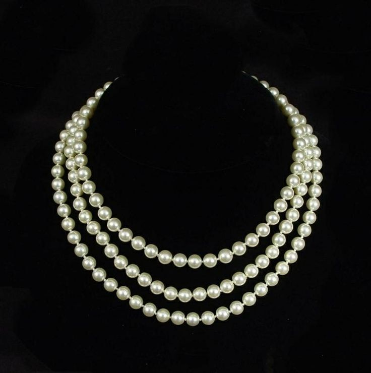 Jackie's legendary faux-pearl necklace was hand knotted on silken cord and carries 158 ivory cream-colored Czechoslovakian glass hand-painted pearls. It is believed that she inherited this necklace from her mother. Jackie was a fan of designer Coco Chanel, who had designed this style of pearls where the three lengths are not uniformly set. Jackie and John, Jr. were captured in a photo where he plays with his mother's pearls.