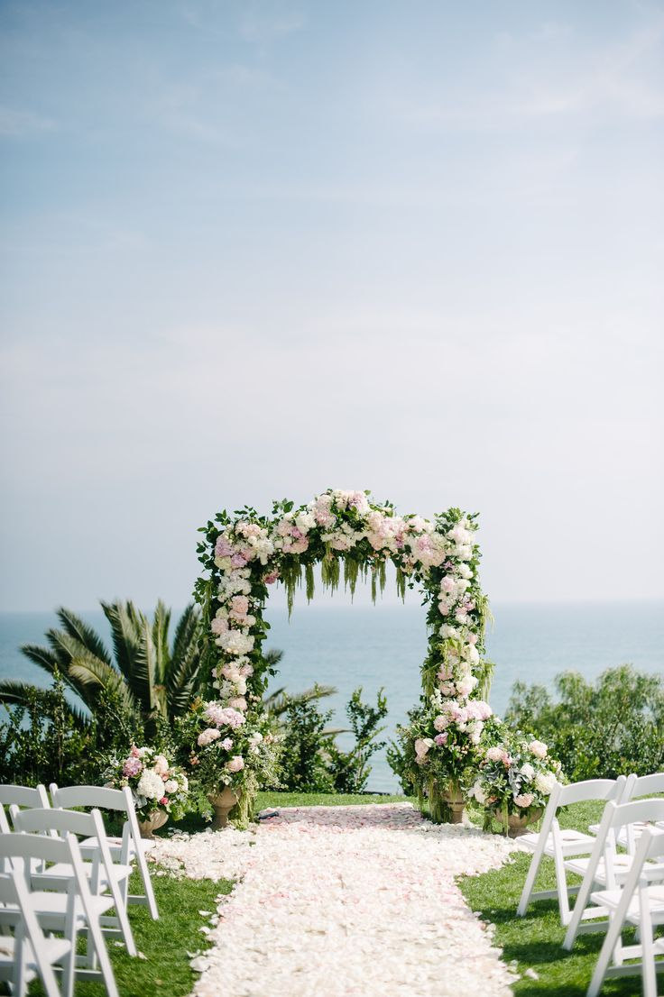 Lush Petal Aisle and Floral Arbor  Photography: Heather Kincaid Read More: http://www.insideweddings.com/weddings/international-couple-weds-in-floral-ceremony-with-ocean-views/847/