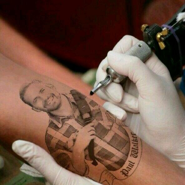 Someone tattooing Paul on arm
