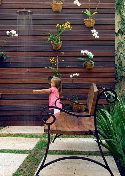 Ao fundo, as orquídeas dão cor ao painel vertical de madeira, que recebeu um chuveirão para refrescar as crianças nos dias de calor. Projeto da paisagista Irene Cisneros