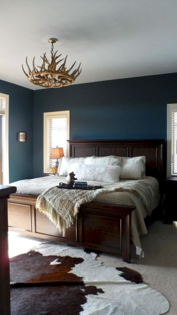 Deep Blue Walls with Antler Chandelier and Cow Hide Rug