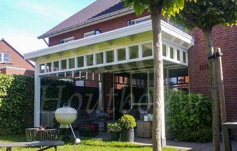Jaro Houtbouw gespecialiseerd in jaren 30 veranda's   Houten overkapping aan huis met raamwerk tussen de staanders