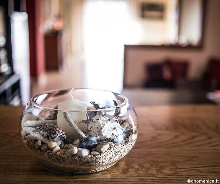 Centrotavola con elementi marini. Come realizzare con una piccola spesa un centrotavola originale e di gusto con elementi marini,  utilizzando un vaso in vetro Happycasa, una candela color avorio Leroy Merlin e il ricordo di un'estate tra sabbia, sassolini colorati e conchiglie.