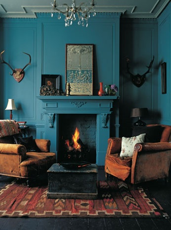 Intense deep teal walls and fireplace with earth brown and red furniture and accessories and antiques plus antlers