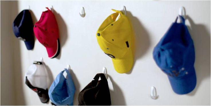 If you have white walls and no hat storage space, we can solve both problems! Place Command™ Hooks on your walls to store your hats. Bonus- they decorate the white walls too!