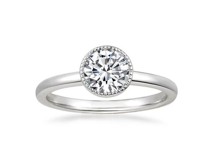 """Festina"" Solitaire Diamond Engagement Ring This striking ring features a gorgeous center diamond bezel set and slightly lofted within an intricate milgrained halo for a brilliant sparkle.  The distinctive and beautifully detailed gallery lends exceptional appeal."