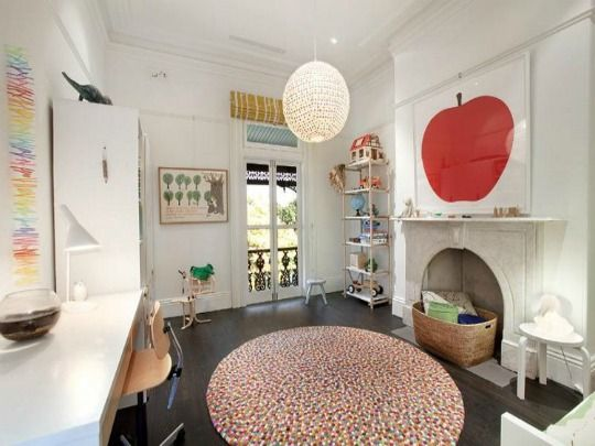 high ceilings, natural light, and plenty of floor space on which to play. The colorful rug, similar lighting fixtures, and the Enzo Mari apple and pear prints