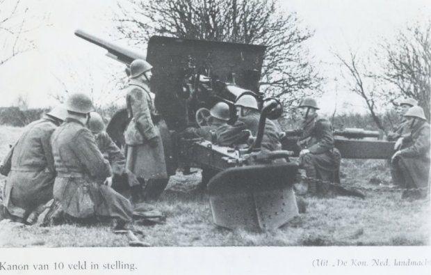 De bemanning van een Bofors 10 cm veldkanon bij het in stelling gebrachte stuk.