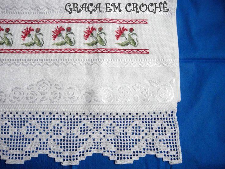 Toalha de rosto da marca Karsten bordada em ponto cruz com o avesso perfeito de cravos vermelho e barrado em crochê no formato de laço