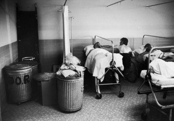 """"""" At the Bronx VA hospital veteran Frank Stoppiello, wounded in the Ashau Valley in Vietnam, gives a cigarette to quadriplegic Andrew Kmetz, an Army veteran, as they wait for treatment. Because of overcrowding, they must share a corner with trash..."""