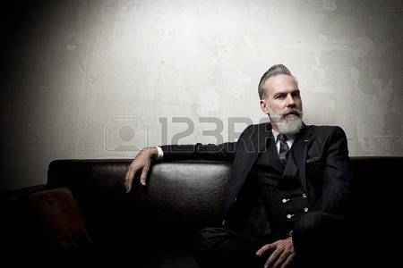 gentlemen: Portrait of adult businessman wearing trendy suit and sitting modern studio on leather sofa against the empty wall.