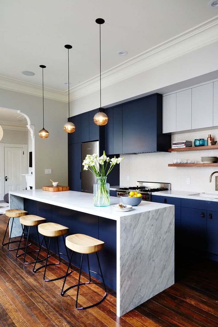 The dark blue cabinets of this modern kitchen bring in a touch of sophisticated fun and help bring out the darker flecks in the marble island.
