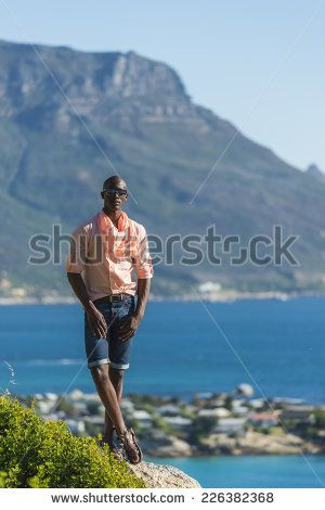 http://www.shutterstock.com/pic-226382368/stock-photo-african-black-man-standing-on-a-high-rock-overlooking-cape-town-as-he-points-and-scouts-the-blue.html?src=WuffEuvvGWj02MQSGcnIHQ-1-19 African Black Man, Standing On A High Rock Overlooking Cape Town As He Points And Scouts The Blue Sky, Ocean And Mountains On A Sunny Summers Day Stock Photo 226382368 : Shutterstock
