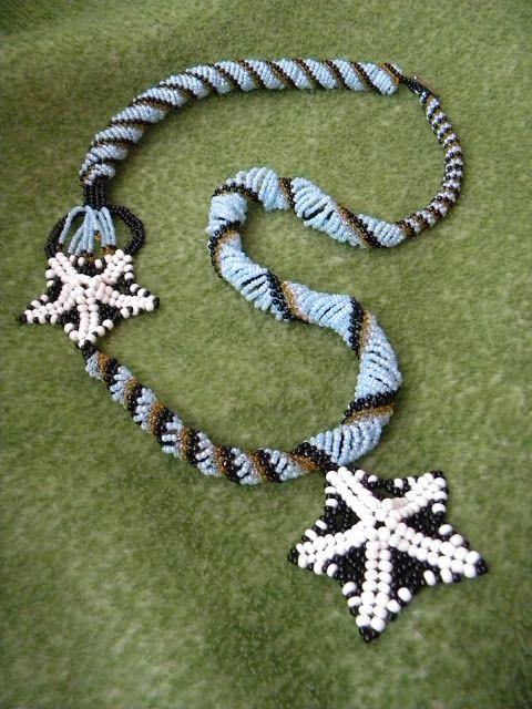 UNICAT  Margelute de nisip de 2 si 4 mm, negre, bleu, albe, galbene, intr-un colier handmade  lung in care s-au prins doua stelute de mare. Lungime 85 cm.
