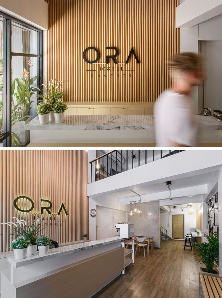 Inside this modern hostel in Bangkok, there's a small reception area with a double-height wood accent wall. Further into the reception area, there's multiple seating options for meeting friends.