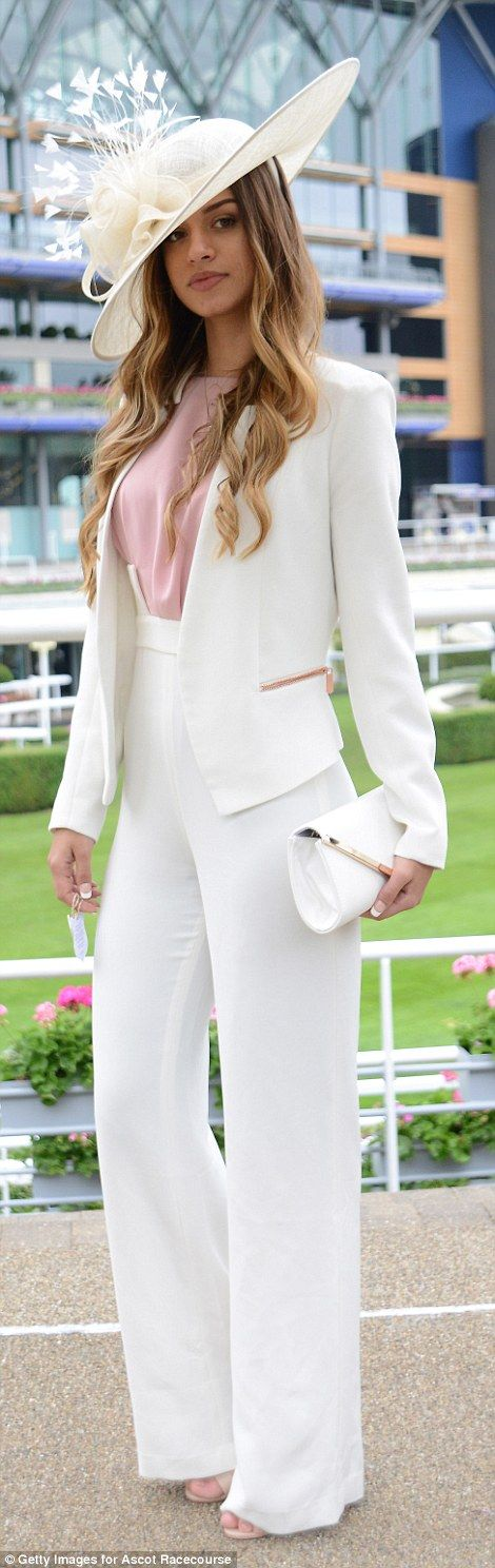 A racegoer stunned in an elegant white trouser suit...