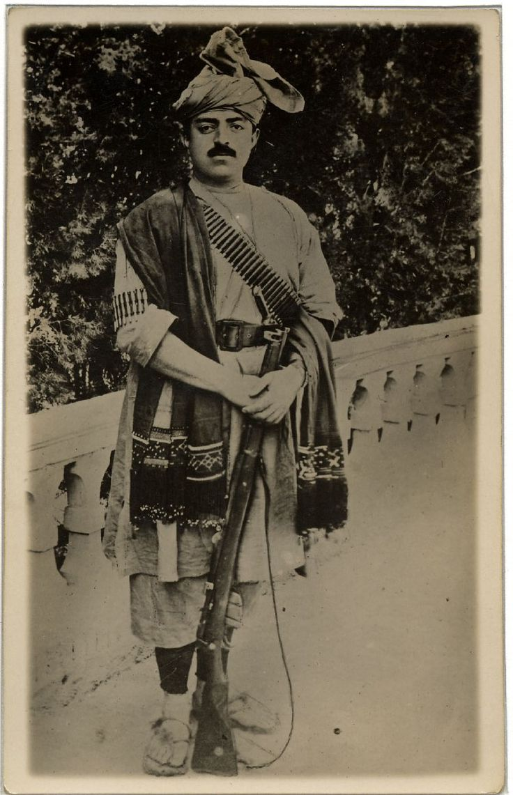 Portrait of King Amanullah Khan of Afghanistan (1892-1960), standing in Afghan native dress and holding a rifle in front of a low balustrade.