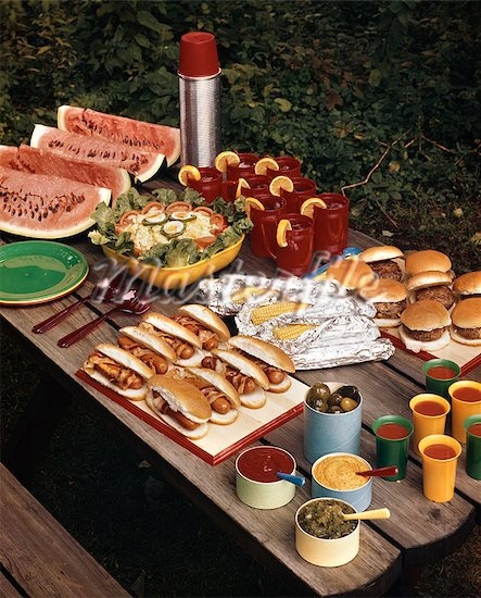 1950s PICNIC TABLE TOP FULL OF FOOD CORN HOT DOGS HAMBURGERS WATERMELON SALAD THERMOS CONDIMENTS BACKYARD SUMMER MEAL Stock Photos