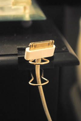 If you like to charge your electronics on your nightstand, attach a binder clip to the side. Thread the charger through the clips, and ta-da—almost as if by magic, your cord will never be lost to the monsters beneath your bed. Read more on housebeautiful.com