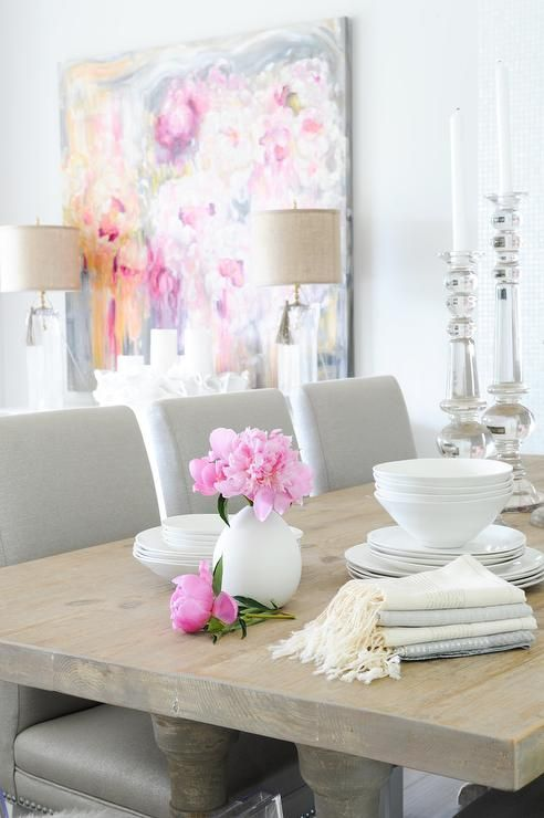 Beautiful dining room features a salvaged wood dining table lined with gray dining chairs next to a white buffet cabinet topped with clear glass tasseled lamps under a pink and gray abstract art piece.
