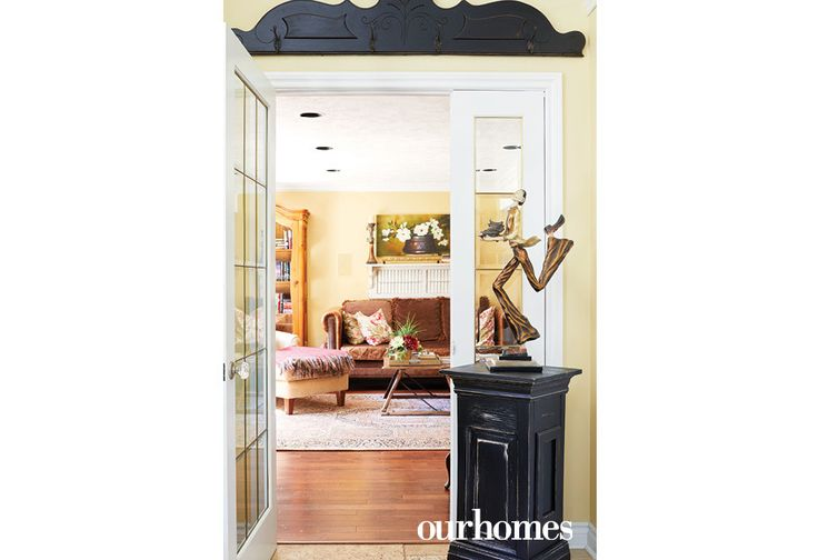 """Whimsical touches appear throughout the house, such as this dashing statuette. Black architectural accents and a black plinth mark this doorway.    See more of this home in """"Elora Homeowners Add Character in Spades"""" from OUR HOMES Wellington-Dufferin Summer 2017: http://www.ourhomes.ca/articles/build/article/elora-homeowners-add-character-in-spades"""