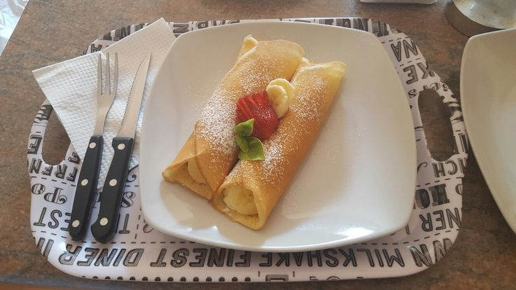 Crepes with slittered strawberries, bananas and cream