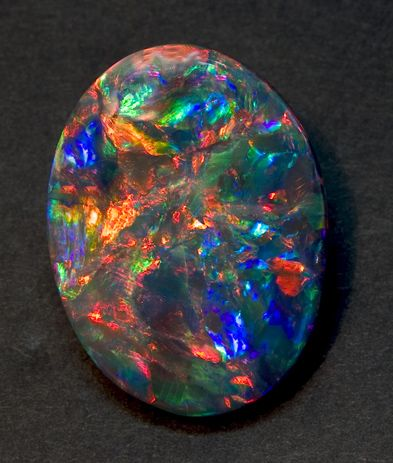 "Black Opal is a greenish type of opal with black mottling and gold flecks. Usually found in ancient hot springs, the gem is usually tumbled smooth and cut cabochon. The phrase in the North ""Black as a black opal"" means, effectively, not very black (or evil) at all, and is used to describe good-hearted rogues and similar individuals who would be embarrassed by praise. A typical specimen has a base value of 1000gp."