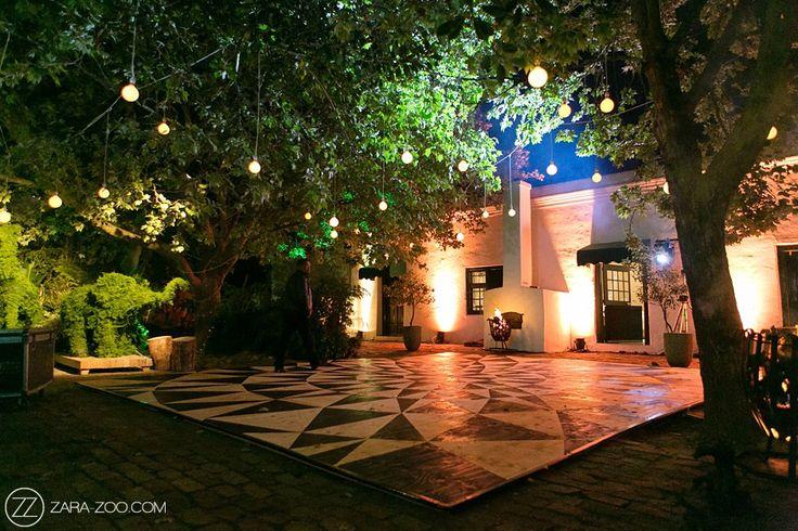 Outdoor wedding dancefloor lighting. Naked bulbs hanging from trees, uplighting agains the venue walls.