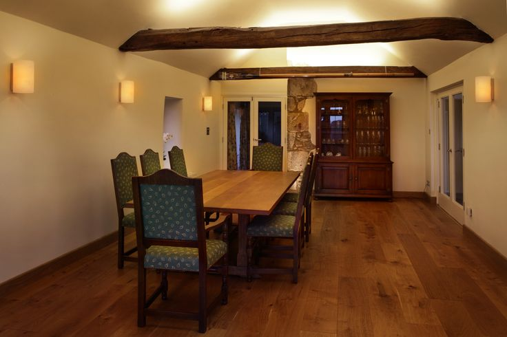 LED ribbon on the top of these original beams in a listed farmhouse dining room create soft background lighting.  Simple wall lights create a peripheral atmospheric light.