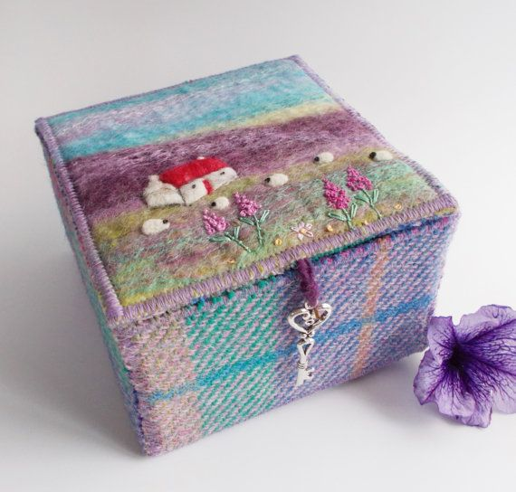 Harris Tweed and Felt Trinket Box, Handmade  I have made this box using my own handmade felt and Harris Tweed. The design on the lid is made using wet felt and needle felting techniques. Little flowers have been embroidered by hand.  The walls of the box are reinforced with thick card to make them sturdy. The lid is weighted down with a silver tone key. As the box is textile there will always be gaps around the edges of the lid.  Box measures 11 x 11 x 7 cm and comes gift wrapped in a brown…