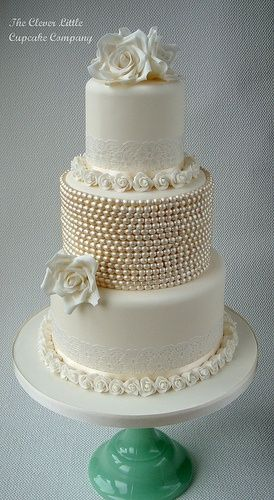 OR Davina, an all white cake w/ light metallic gold pearls lining the bottoms of each layer and gold figs placed strategically ...