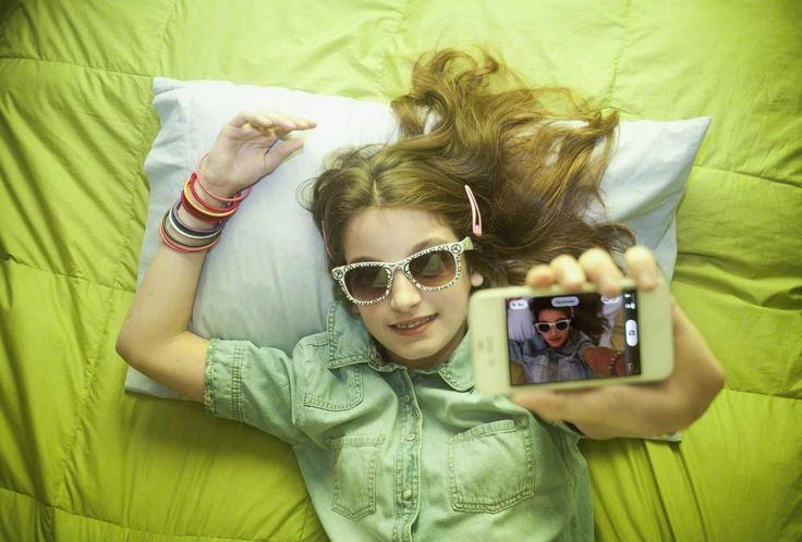 Girl taking self-portrait with smartphone --- Image by © Curi Hyvrard/Corbis