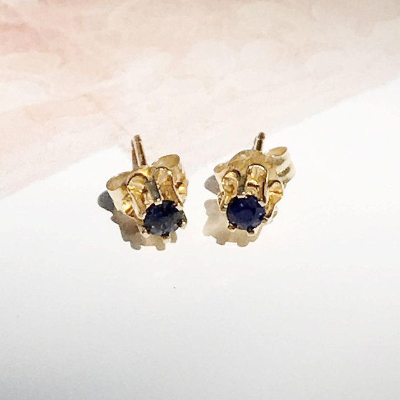 Teeny tiny and so versatile - sapphire stud earrings, in a stormy, moody, deep shade of blue. These earrings are meant for just the slightest splash of blue, perhaps for the vintage bride or the woman with multiple piercings who is looking for small and unique studs to layer with others. These would also be perfect for a child needing some starter earrings after getter her ears pierced.  HISTORY: These are more modern estate pieces, lighter vintage  MATERIALS: 14k gold, sapphire  SIZE: Very…