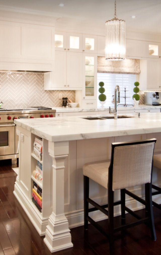 Cookbook storage in island, gray herringbone tile backsplash, white kitchen