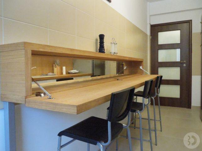 Spatiul mesei care se deschide oferind depozitare si loc de luat masa; scaunele aferente sunt de la IKEA si au fost taiate pentru a se potrivi cu inaltimea mesei; in plus ele se pot pune unul peste altul atunci cand nu sunt folosite