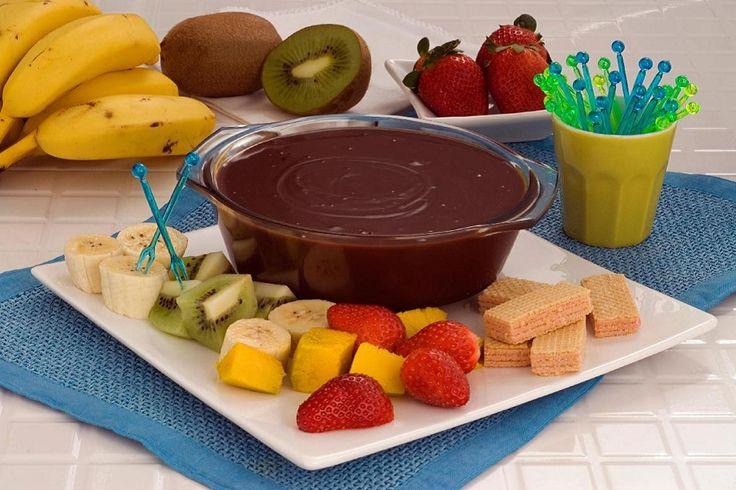 Na foto, o fondue de travessa está acompanhado de frutas fatiadas e biscoitos wafer em um prato de servir branco.