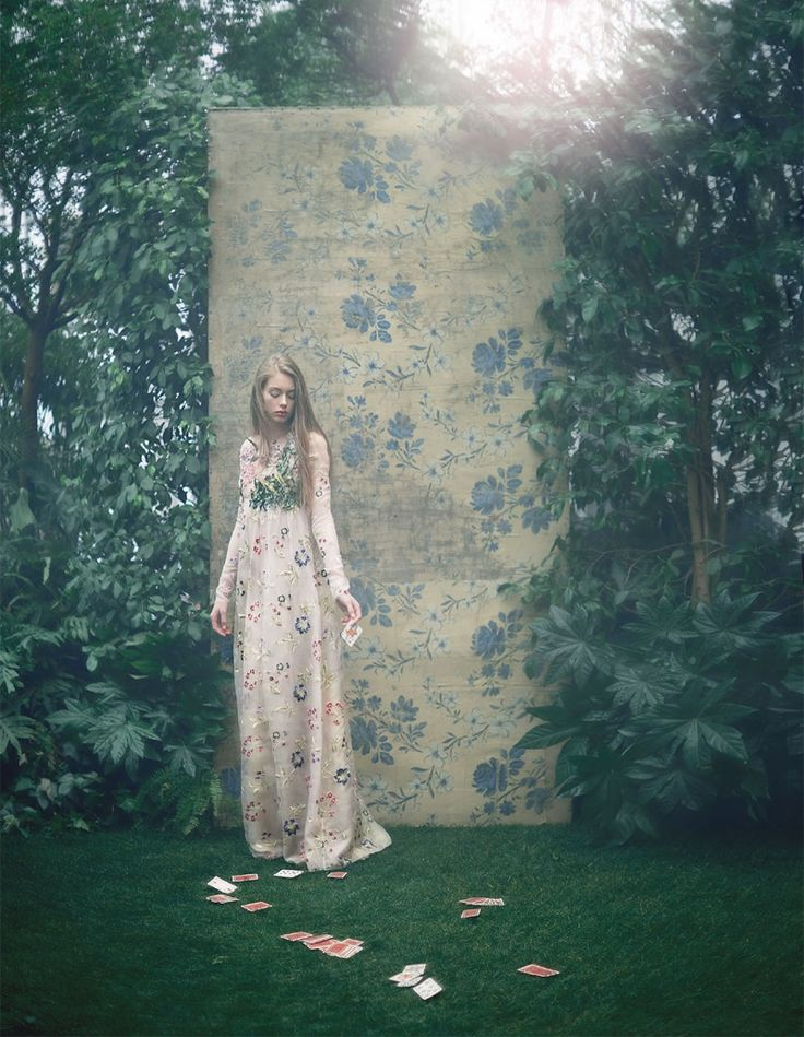 Surrounded by green shrubbery, Lauren models a long-sleeve Giambattista Valli gown embellished with florals