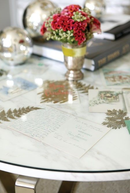 Not just for holiday display, a table topped with a piece of tempered glass to fit can showcase any number of items year-round.  Here, a collection of vintage Christmas cards with sentimental value are on show. Some cards are displayed open so that the message inside can be read.