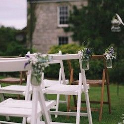 A mixture of white and wooden vintage folding chairs for an outdoor wedding ceremony in Cornwall with jam jars filled with flowers on the aisle chairs.