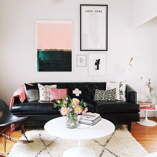 A pink and black livingroom color scheme with color coordinating art. Interior Design inspiration.