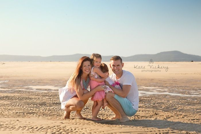 Family photography, family pose, outdoor location, beach, sand, natural light, family of four, beautiful location, family embrace, embrace