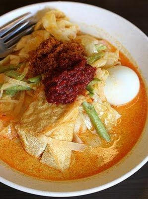 Lontong. A Malay dish. Hard boil egg, bean curd, long beans, cabbage, steamed rice cakes, in watery curry.