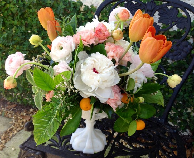 Vintage white footed compote holds arrangement of white peony, orange tulips, pink and peach ranunculus , kumquats, cafe au lait dahlias and pink carnations.